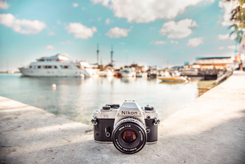 Image of a photo camera, positioned on the ground of a bay, next to the sea and boats.
