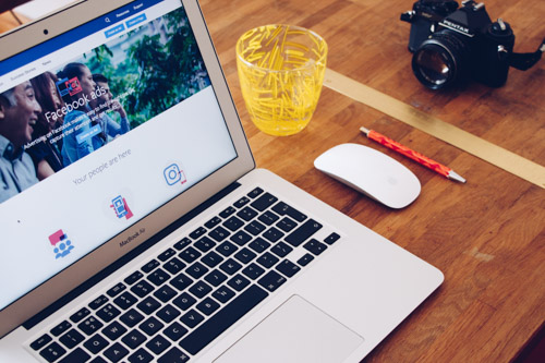 Image of a laptop on a desk, showing on the screen the Facebook Adds - platform for Social Media Marketing